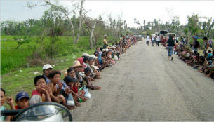 On a road near Pyapon, in an area of Myanmar ravaged by a cyclone, people waited on Sunday for aid from Burmese civilians. Photo: NYT