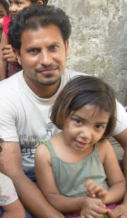 "Ilyas Masih with one of his seven daughters. Feeding so many is not easy. ""I struggle even to buy a single kilo of `atta� [wheat flour], which costs Rs 30 [36 US cents], and even that produces just about half a `roti� [flat bread] for each of us,� he said. For Ilyas�s family, securing each meal - eaten on the floor around a kerosene oil stove on which Nasim cooks - is an ordeal. �Especially at night, it is painful to hear the children beg for more food. Sometimes they snatch food from each other,� Ilyas said. Photo: Kamila Hyat/IRIN"
