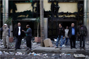 Egyptians in front of the rubble of a looted property in Cairo belonging to Ahmed Ezz, one of the leading figures in the National Democratic Party