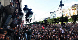 Demonstrators climbed the walls of the Interior Ministry in Tunis on Friday, June 14. Tunisia�s president, Zine el-Abidine Ben Ali, fled his country that night, capitulating after a month of mounting protests calling for an end to his 23 years of authoritarian rule.  Photo: Holly Pickett/New York Times