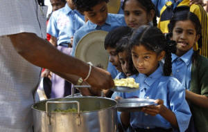 Indian schoochildren receive a free midday meal at a government school in Jammau.  Photo: Washington Post