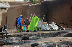 Women and children in front of burned houses in Baga, Nigeria, after as many as 200 civilians were killed in an assault that survivors blamed on soldiers. Photo: Agence France-Presse � Getty Images