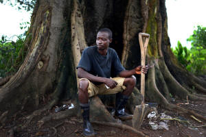 James Hamilton, chief gravedigger at King Tom cemetary in Freetown, sits by a tree with his spade.  Photo: Samuel Aranda for The New York Times