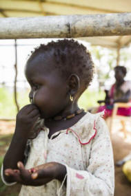 A child snacks in her family�s new shelter, at Protection of Civilians (POC) camp III, near UN House, in Juba. Photo: UN Photo/JC McIlwaine